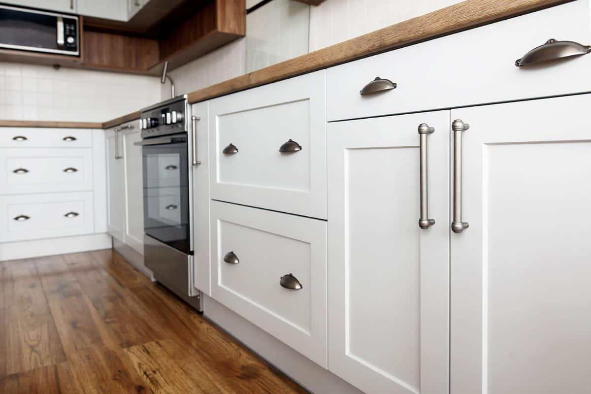 White kitchen cabinets with stainless steel handles and cup handles, Where Should Kitchen Cabinet Knobs And Handles Be Placed?