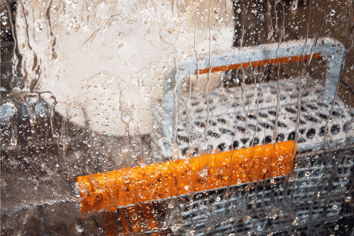 wet glass window of a dishwasher in operation